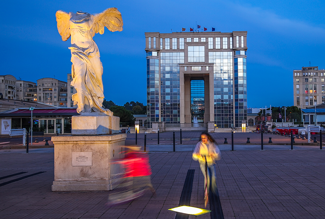 Photographie de deux enfants en train de faire de la trottinette devant l'Hotel de Région de Montpellier